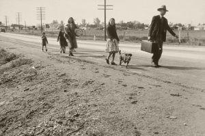 family walking along a dirt road carrying belongings