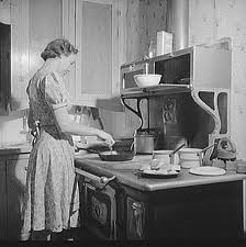 woman standing before an old-fashioned stove