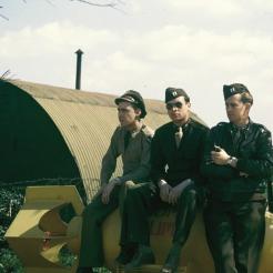 Three GIs sitting on a bomb at Attlebridge airfield. © John Michael