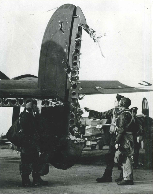 Crew members of 'QUEENIE' a 735th B.S. B-24H (41-28631) inspect the damage caused by a direct flak hit during a mission to V. weapons sites on the French coast on 20th April 19444.