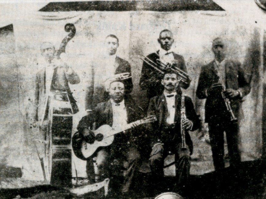 The only photograph of the Buddy Bolden Band, c. 1903-05, with Bolden standing next to bassist cropped